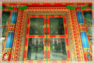 A fresh red glass door in a temple in Lumbini, Nepal