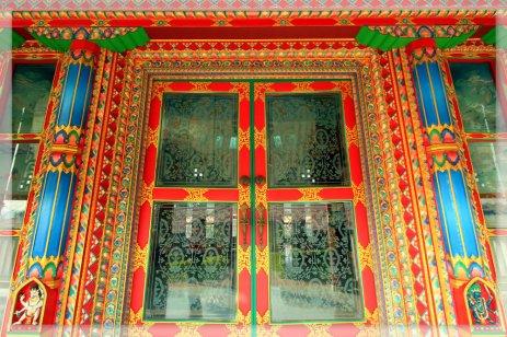 A fresh red glass door in a temple in Lumbini, Nepal