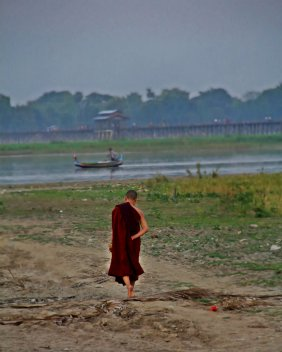 A young monk walked alone near U Bein Bridge